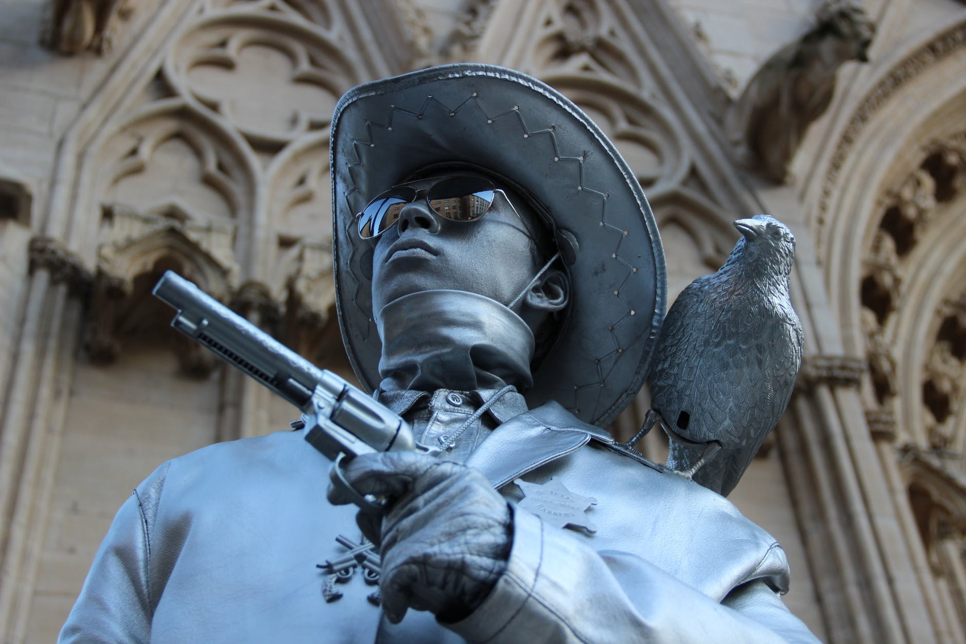 selective focus photography of cowboy holding revolver pistol statue