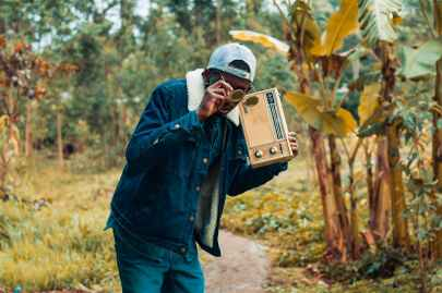 man holding brown boombox radio