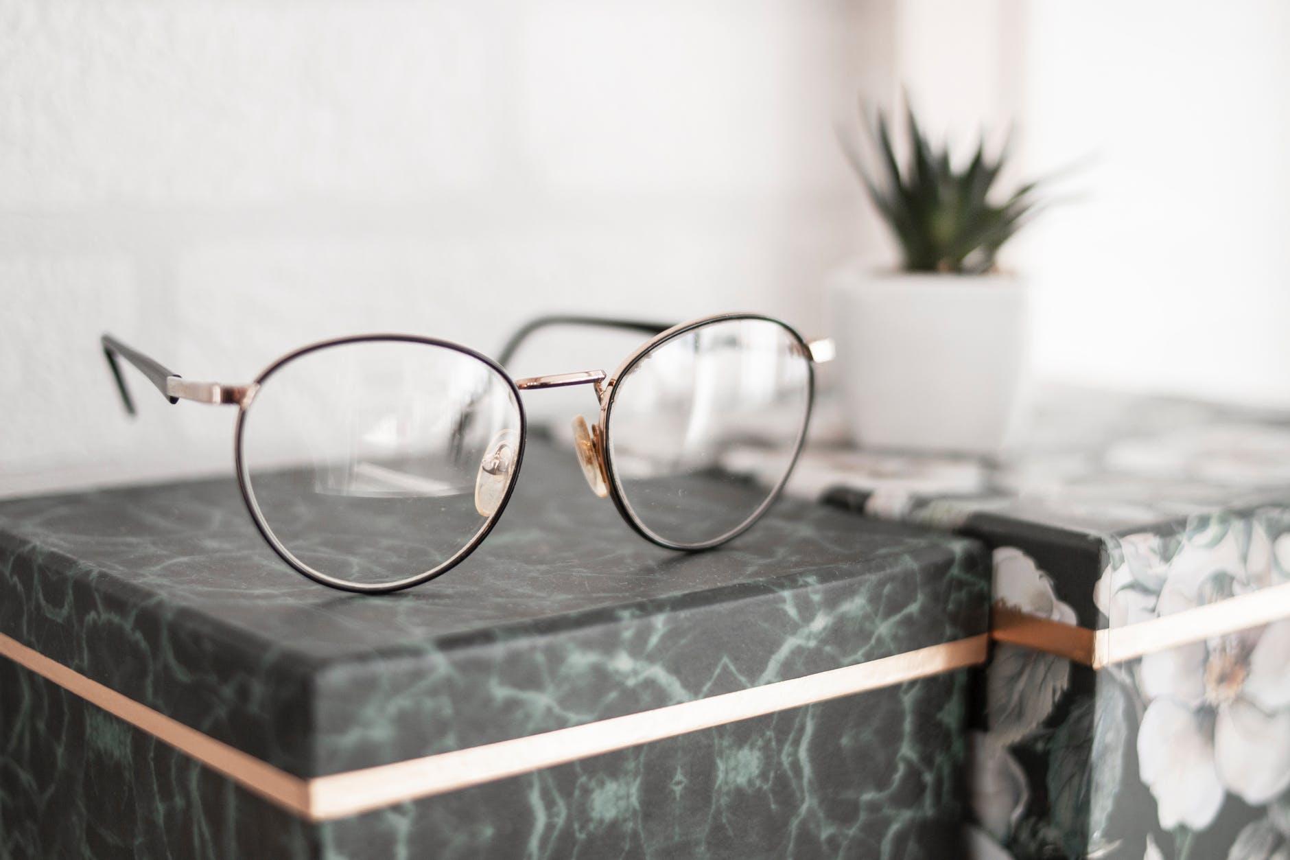 gray framed eyeglasses on black surface