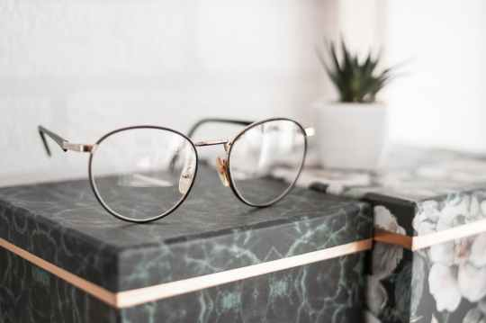 gray framed eyeglasses on black surface