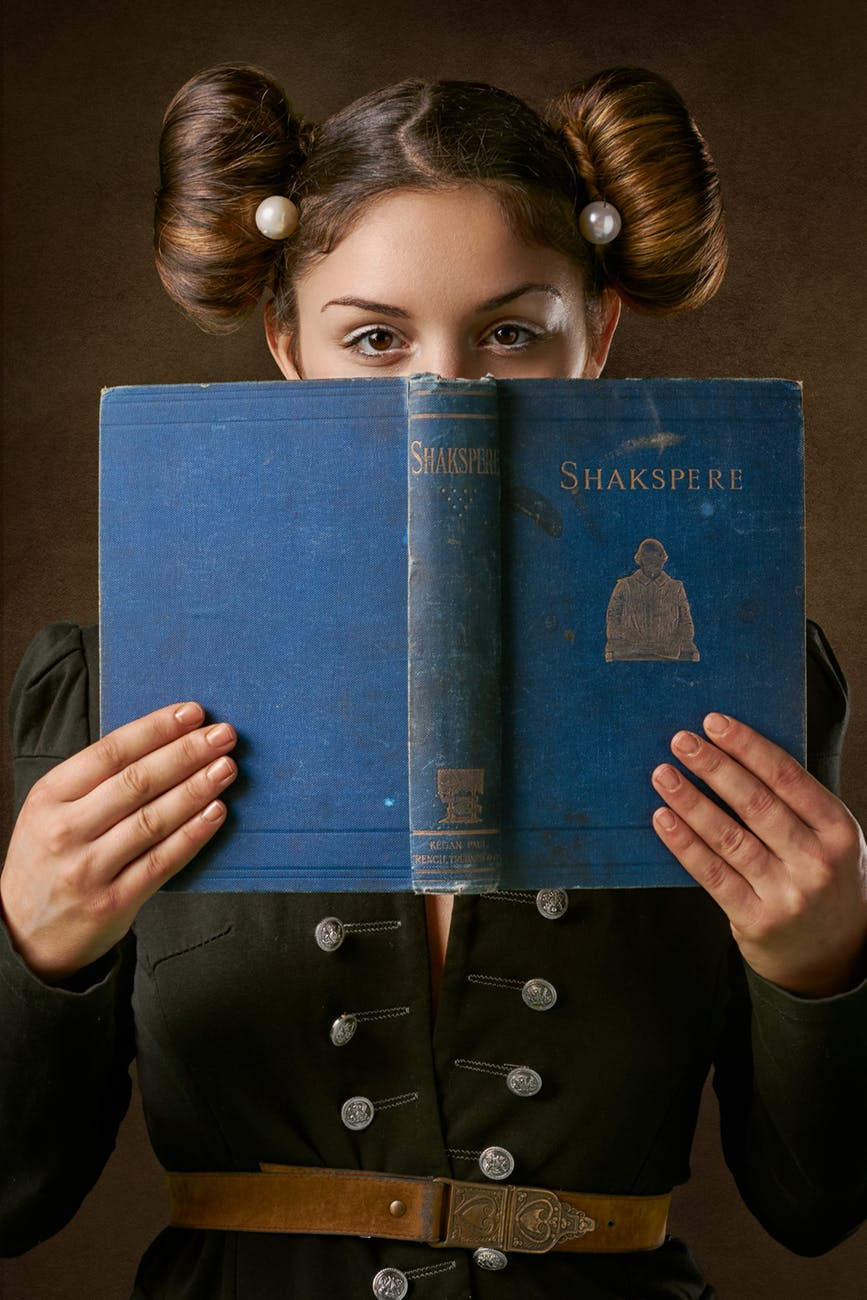woman holding blue shakspere book over face