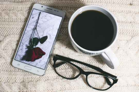 phone near mug and eyeglasses on table