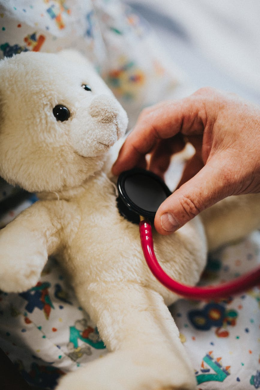 person using stethoscope on bear plush toy