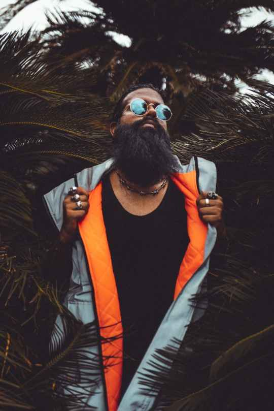 man wearing grey and orange zip up vest beside palm plant